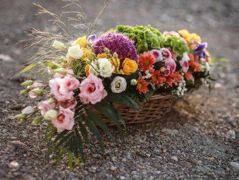 Coș în formă ovală umplută cu multe flori de vară